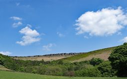Long range view of the tops of Stannage Edge 2 and meadowland in Haversage. Taken on a sunny spring day, capturing gentle white clouds against an ideal blue sky Royalty Free Stock Image
