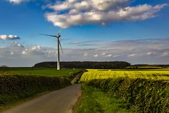 Country lane leading to a wind turbine Stock Image