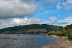 Clouds gather over the dry slopes of Lady Bower reservoir in late summer. Taken to capture the scale of the water`s retreat at the Lady Bower reservoir, within royalty free stock photo