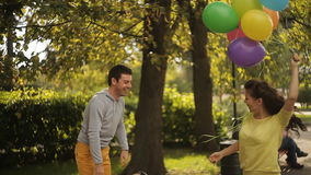 She takes the guy balloons. A couple in love in the park with colorful balloons stock video footage