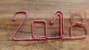Takes the number 2018 with pink wire from the wooden table with finger stock video