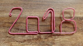 Takes the number 2018 with pink wire from the wooden table with finger stock video footage
