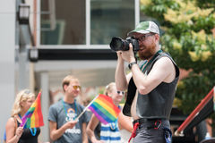 A takes pictures while walking in the Gay Pride Parade. A man takes photos with his camera while in the gay pride parade - Des Moines, Iowa Royalty Free Stock Photography