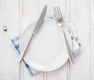 Takes zenithal of empty plate, and metal cutlery, on table Royalty Free Stock Photos