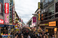 Takeshita Street in the Harajuku district of Tokyo, Japan. Tokyo, Japan - December 6, 2015: Crowds of people walk through Takeshita Street in the Harajuku Royalty Free Stock Photo