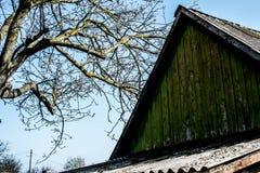 Taket av ett gammalt hus på bakgrunden av himlen arkivfoto
