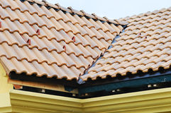 Takhus med det belade med tegel taket på blå himmel detalj av tegelplattorna och hörnbeslaget på ett tak som är horisontal taksky Royaltyfri Foto
