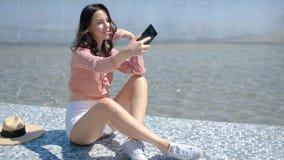 Takin bonito y atractivo de la muchacha una foto del selfie con su teléfono móvil almacen de video