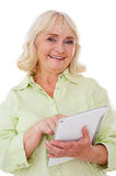 Taking advantages of digital age. Cheerful senior woman using digital tablet and smiling while standing isolated on white background stock images
