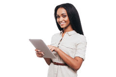 Taking advantages of digital age. Confident young African woman working on digital tablet and smiling while standing against white background stock images
