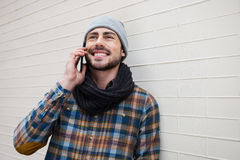 Taking advantages of digital age. Handsome young man talking on the mobile phone and smiling while leaning brick wall stock photo