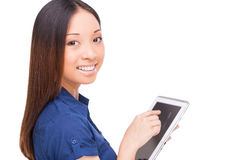 Taking advantages of digital age. Rear view of beautiful young Asian woman using digital tablet and looking over shoulder while standing isolated on white royalty free stock photography