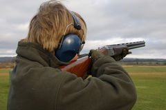 Taking Aim. Teenage boy hold the gun and aims for the clay pigeon target Stock Image