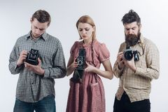 Taking another shot. Paparazzi or photojournalists with vintage old cameras. Retro style woman and men hold analog photo. Taking another shot. Paparazzi or royalty free stock image