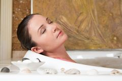 Taking bath. Image of relaxing woman with closed eyes having pleasant bath with seashells near by Stock Photography