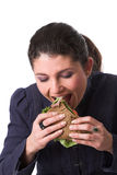 Taking a big bite. Beautiful brunette holding a big sandwich in her hand with salad and roastbeef and taking a big bite Stock Images