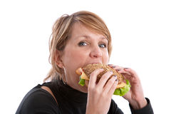 Taking a big bite. Pretty blond woman taking a big bite out of a healthy sandwich Stock Photo