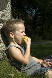Taking a bite. Kid eating a juicy apple while relaxing royalty free stock images