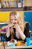 Taking a bite. Blond student sitting in class and taking a bite of her healthy sandwich Stock Photo
