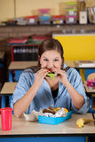 Taking a bite. Young schoolgirl taking a bite of her healthy lunch Royalty Free Stock Photography