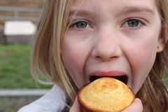 Taking a bite. A 6 year old blonde girl with blue eyes taking a big bite of a corn muffin stock image