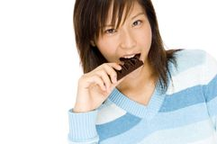 Taking A Bite. A cute young asian woman taking a bite on a bar of chocolate Royalty Free Stock Image