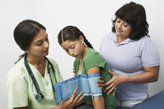 Taking Blood Pressure. Female doctor taking teenage girl's blood pressure with the help of the patient's mom stock image