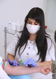 Taking a blood sample. Laboratory with nurse taking a blood sample from patient royalty free stock photography