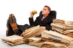 Taking a break. Business man taking a break during a hard work with papers, his foots on table and eating a sandwich Royalty Free Stock Photos