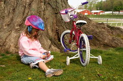 Taking a break. A young girl taking a break by a tree royalty free stock image