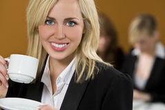 Taking A Break. An attractive young female executive takes a coffee break while her colleagues work on a laptop behind her royalty free stock photos