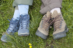 Taking a Break. Closeup of two pairs of legs with walking boots of mother and daughter sitting in the grass taking a break after a hike Stock Photo