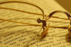 Taking a break. Old pair of gold framed glasses resting on a book stock images