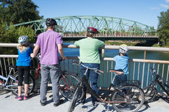 Taking a Break on the Bridge. A young family takes a break on a bike bridge as they look up the river stock images