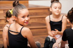 Taking a break from dance class. Pretty little Hispanic girl and her friends taking a break from dance class and smiling royalty free stock images