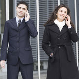 Two businesspeople calling outside. Taking a break in the office royalty free stock image