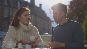 Taking a Break from Shopping. Young couple enjoying a cup of tea together in a cafe. They are sitting outdoors stock video
