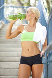 Taking a break to rehydrate. An athletic woman resting and drinking from a water bottle after a workout Royalty Free Stock Photography