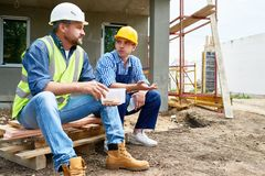 Taking Break from Work. Two workers wearing protective helmets taking break from work and enjoying lunch while sitting outdoors, unfinished building on Royalty Free Stock Image