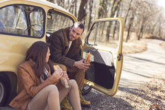 Taking a break. Young couple taking a break on their road trip, sitting in the car by the road and eating sandwiches. Focus on the guy Stock Image
