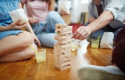 Taking brick out. Tower of wooden bricks on the floor and several friends around it during play Royalty Free Stock Images