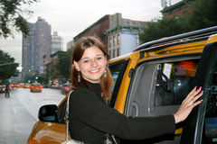 Taking the Cab. Young woman entering a taxi cab in the city Royalty Free Stock Photo