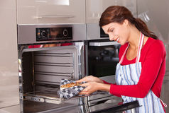 Taking the cake. Attractive young woman taking her baked cake out of the oven Royalty Free Stock Photography