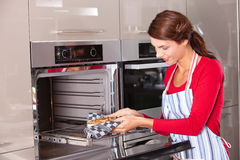Taking the cake out. Brunette taking the cake out of the oven Royalty Free Stock Image