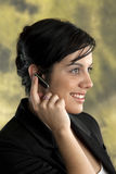 Taking a Call. Young pretty business woman taking a call using her bluetooth device Royalty Free Stock Images