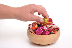 Taking Candy from a bowl. Photograph of candy in a bowl and a hand taking one out Royalty Free Stock Photo