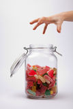 Taking candy from a jar Royalty Free Stock Images