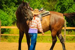 Cowgirl getting horse ready for ride on countryside stock photos