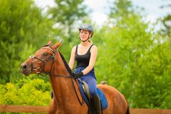 Jockey girl doing horse riding on countryside meadow. Taking care of animals, horsemanship, western competitions concept. Jockey girl doing horse riding on royalty free stock photo