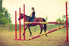 Jockey young girl doing horse jumping through hurdle. Taking care of animals, horsemanship, western competitions concept. Jockey young girl doing horse jumping stock photography